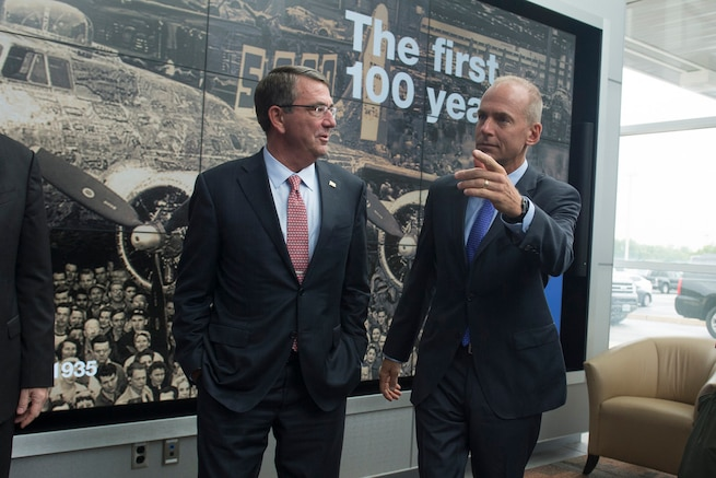 """Defense Secretary Ash Carter, left, speaks with Dennis Muilenburg, president and chief executive officer of The Boeing Company as Carter arrives in St. Louis, Mo., to speak with workers at Boeing and kick off the Defense Advanced Research Projects Agency's """"Wait, What?"""" future technology forum, Sept. 9, 2015. DoD photo by U.S. Air Force Senior Master Sgt. Adrian Cadiz"""
