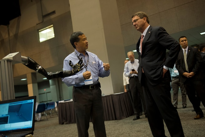 """Defense Secretary Ash Carter, right, is briefed on the robotic limb exhibit at the Defense Advanced Research Projects Agency """"Wait, What?"""" future technology forum at the America's Convention Center Complex in St. Louis, Mo., Sept. 9, 2015. DoD photo by U.S. Air Force Senior Master Sgt. Adrian Cadiz"""
