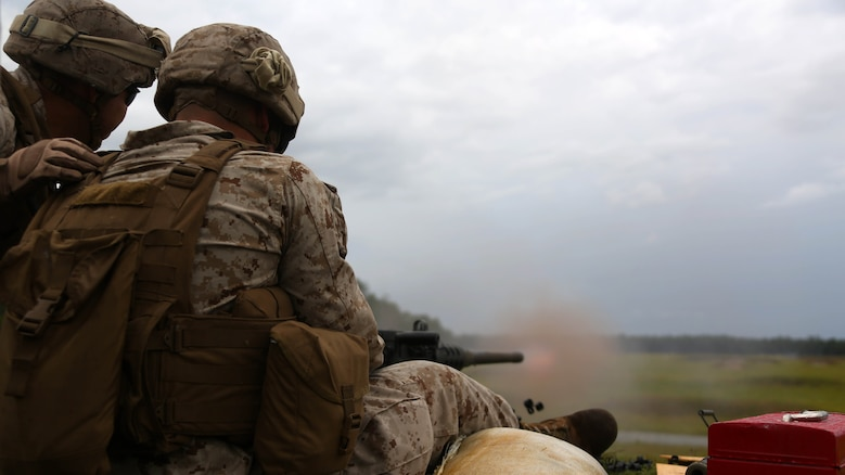 Sgt. David Sosa, left, assists Cpl. Gerardo Lopez Ortiz with firing a Browning M2 .50-caliber machine gun down range during a weapons familiarization range at Marine Corps Base Camp Lejeune, North Carolina, Aug. 27, 2015. More than 100 Marines from Marine Air Support Squadron 1 honed their weapons skills with the M240B machinegun, Browning M2 .50-caliber machine gun and the M1014 combat shotgun. Marines from various military job occupations received hands-on experience that allows them to improve crucial skills and become well-rounded war fighters. Sosa and Ortiz are air support operations operators with MASS-1.