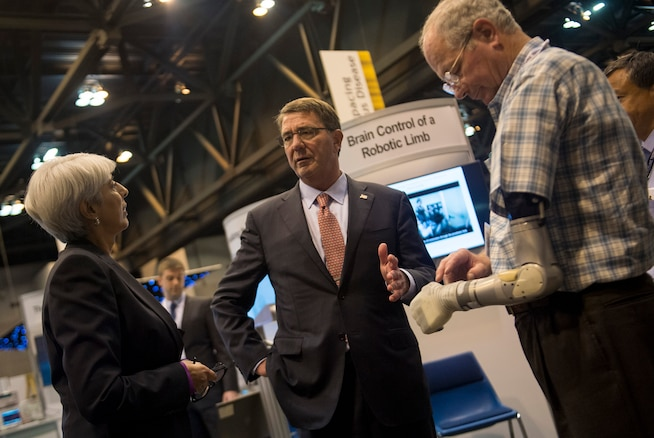 """Defense Secretary Ash Carter speaks with Arati Prabhakar, Director of the Defense Advanced Research Projects Agency, as they view the robotic limb exhibit and demonstration at DARPA's """"Wait, What?"""" future technology forum at the America's Convention Center Complex in St. Louis, Mo., Sept. 9, 2015. DoD photo by U.S. Air Force Senior Master Sgt. Adrian Cadiz"""