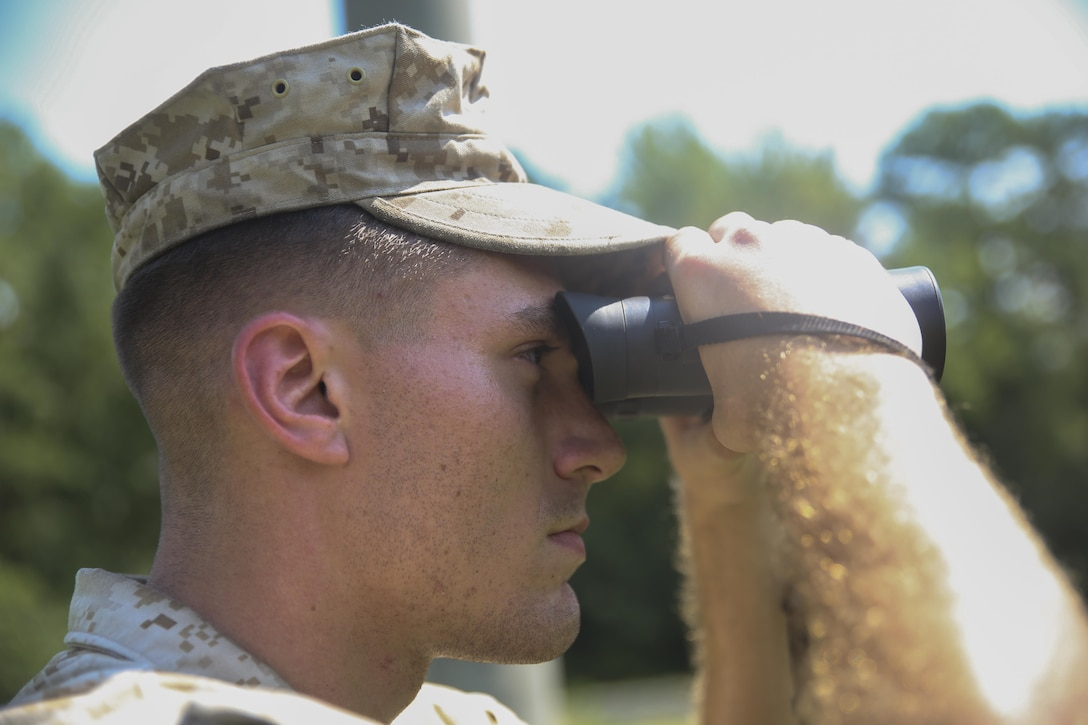 Cpl. Bryce Navarre, an infantryman with 2nd Battalion, 6th Marine Regiment, observes an area using binoculars to aid him in seeing objects at greater distances during an observation lanes sweep aboard Camp Lejeune, North Carolina, Sept. 03, 2015. The Marines were given binoculars to allow them in locating simulated IEDs from a safe distance. (U.S. Marine Corps photo by Lance Cpl. Chris Garcia/Released)