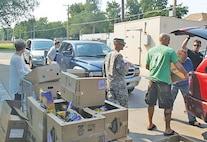 """Soldiers from the 97th Military Police Battalion volunteer with their local community partners, the people from the Flint Hills Breadbasket in Manhattan, Kansas.  The organization is funded on volunteer help and donations to hand out food in their """"Drive-Thru"""" event Aug. 25.  There were stations set up along the warehouse with different types of non-perishable goods.  Each Soldier posted at a station, divided out food based on the household size, and placed it in the recipients' cars.  This is an excellent opportunity afforded to our Soldiers to actively give back to the community, said battalion commander Lt. Col. Alexander Murray."""
