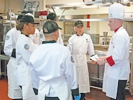Sgt. Michael Allen, the 1st Infantry Division's senior culinary instructor, speaks to Refresher Training students ahead of their end-of-course luncheon.