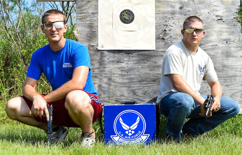 U.S. Air Force Staff Sgt. Jeremiah Jackson, (right), 23d Equipment Maintenance Squadron aircraft metals technology craftsman, and Senior Airman Ian Pitts, 23d EMS munitions flightline delivery crew chief, pose for a photo after pistol shooting practice Sept. 4, 2015, in Valdosta, Ga. Jackson, a member of the Air Force's National Pistol Team, took Pitts underneath his wing as his protégé to help him perfect his pistol shooting techniques in preparation for team camp.  (U.S. Air Force photo by Senior Airman Ceaira Tinsley/Released)