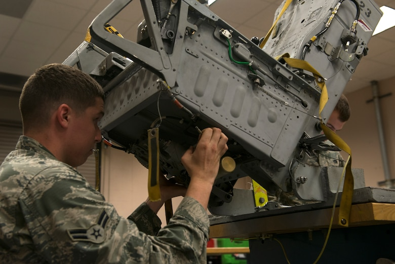 U.S. Air Force Airman 1st Class Caleb Luna, 23d Component Maintenance Squadron aircrew egress systems journeyman, reinstalls a seat pan on an ejection seat Sept. 2, 2015, at Moody Air Force Base, Ga. An A-10C Thunderbolt II seat contains 13 explosives in order to eject it out of the aircraft in case of an emergency. (U.S. Air Force photo by Airman 1st Class Kathleen D. Bryant/Released)