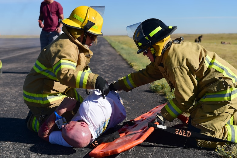 Bennett Fire Department first responders move a simulated casualty onto a stretcher Sept. 10, 2015, at Front Range Airport, Colo. A joint operation was conducted by Buckley Air Force Base and surrounding community emergency responders during an annual major accident response exercise. (U.S. Air Force photo by Airman 1st Class Luke W. Nowakowski/Released)