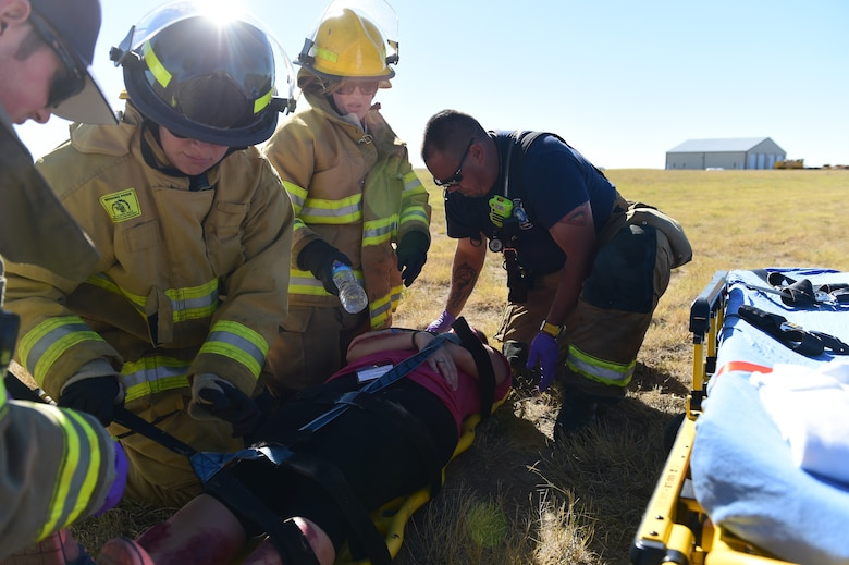 Bennett Fire Department first responders help secure a simulated casualty Sept. 10, 2015, at Front Range Airport, Colo. A joint operation was conducted by Buckley Air Force Base and surrounding community emergency responders during an annual major accident response exercise. (U.S. Air Force photo by Airman 1st Class Luke W. Nowakowski/Released)