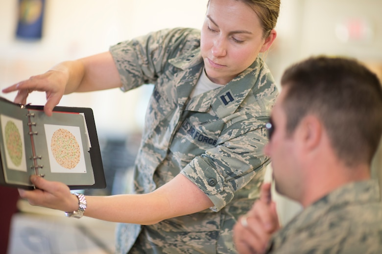 U.S. Air Force Capt. Marcy O'Neil, from the 158th Fighter Wing Medical Squadron, administers a vision exam at the Vermont Air National Guard in South Burlington, Vt., June 6. The 158th Medical Squadron has become the first Air Guard base to process both Preventative Health Assessments and Occupational Health Physical Examinations in one large push, improving the medical experience for both sides, and creating a cost-saving and efficient format for other bases to emulate. (U.S. Air National Guard photo by Senior Airman Jon Alderman)