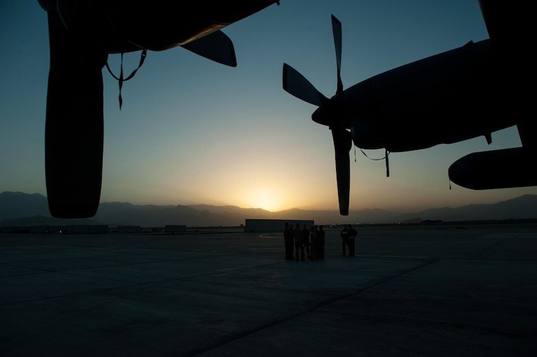 U.S. Airmen assigned to the 41st Expeditionary Electronic Combat Squadron talk during an EC-130H Compass Call aircraft final mission meeting on the flight line at Bagram Airfield, Afghanistan, Sept. 6, 2015.  The Compass Call is an airborne tactical weapon system using a heavily modified version of the C-130 Hercules airframe. (U.S. Air Force photo by Tech. Sgt. Joseph Swafford/Released)