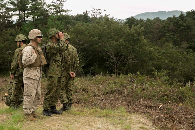 Japanese Ground Self-Defense Force Col. Tadisha Tanida, middle right, and U.S. Marine Lt. Col. Eric Reid look at targets while Marines fire the shoulder-launched multipurpose assault weapon during Forest Light 16-1 at Camp Imazu, Takashima, Japan, Sept. 7, 2015. The JGSDF and U.S. Marines took turns sharing knowledge about different anti-tank missile systems. After giving specifications of their respective weapon systems, the two forces used practice rounds to demonstrate how well the weapon systems work. Forest Light will take place Sept. 7-18 with approximately 240 Marines working next to 350 JGSDF members. The exercise will consist of mortar live fire, establishing forward arming and refueling points training, helicopter borne skills and combined arms procedures. Tanida is the commanding officer of the 50th infantry regiment, 14th Brigade, JGSDF. Reid is the commanding officer of 1st Battalion, 2nd Marine Regiment currently assigned to 4th Marine Regiment, 3rd Marine Division, III Marine Expeditionary Force.