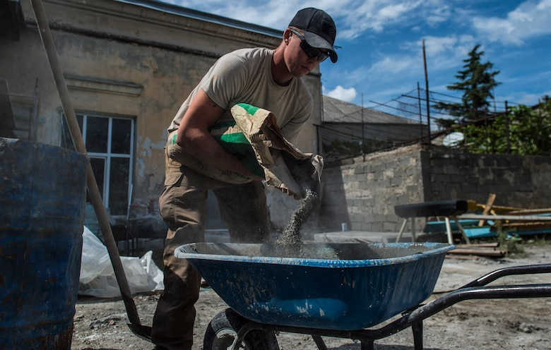 Airman 1st Class Cole Kasten, a 52nd Civil Engineer Squadron pavement and heavy equipment operator, mixes cement for a ramp at Public School No. 4 in Gori, Georgia, Aug. 28, 2015. Kasten and a team of Airmen built the ramp to give disabled students at the school safe access into the gymnasium. Humanitarian and civic assistance projects enhance operational readiness of military personnel while providing mutual support to the host