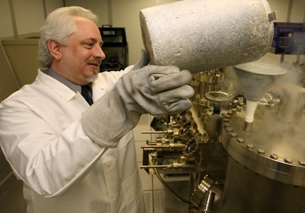 Naval Surface Warfare Center Dahlgren Division (NSWCDD) scientist Dr. Kevin Boulais uses liquid nitrogen in a molecular beam epitaxy system to create photo capacitors for light guide film applications.