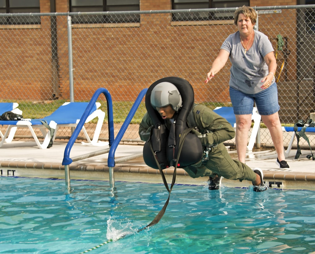 Laura Silver, 80th Operation Support Squadron stabilizes Capt. Brandon Bailey, 459th Flying Training Squadron Euro-NATO Joint Jet Pilot Training instructor pilot, before he gets pulled into the base swimming pool at Sheppard Air Force Base, Texas. Bailey was by a pulley system operated by course instructors as part of the water survival refresher training. The training simulates a parachute water landing after ejecting from a T-38 Talon aircraft. (U.S. Air Force photo by Danny Webb)