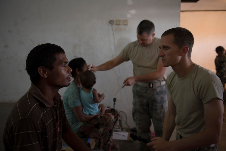 Capt. Davis Staley (front), 673rd Medical Group optometrist, and Master Sgt. Robert Shaw (back), 141st Medical Group optometry technician, examine patients during a Pacific Angel health services outreach Sept. 11, 2015, in Baucau, Timor-Leste. Pacific Angel is a multilateral humanitarian assistance civil military operation, which improves military-to-military partnerships in the Pacific while also providing medical health outreach, civic engineering projects and subject matter exchanges among partner forces. (U.S. Air Force photo by Staff Sgt. Alexander W. Riedel/Released)