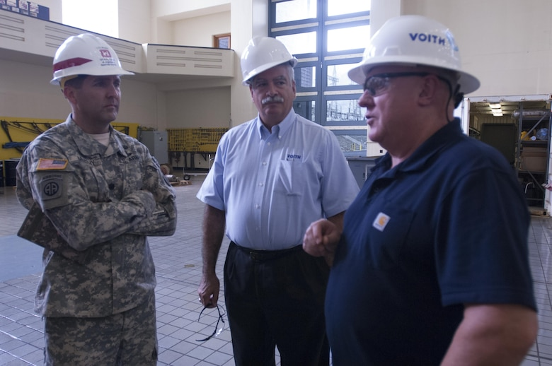 Lt. Col. Stephen F. Murphy (Left), U.S. Army Corps of Engineers Nashville District commander, and Bob Gallo (Center), Voith Hydro chief executive officer, chat with Martin Parker, Voith Hydro site manager, about the ongoing rehabilitation of hydropower unit two at the Center Hill Dam Power House in Lancaster, Tenn., Sept. 9, 2015.