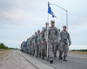 Airmen from 90th Logistics Readiness Squadron march down a base roadway while carrying rucksacks to commemorate the terrorist attacks against the U.S. in 2001, at F.E. Warren Air Force Base, Wyo. Sept. 11, 2015. This marks the fourth year the 90th LRS has made the march in memory of the lives lost that day. (U.S. Air Force photo/Lan Kim)