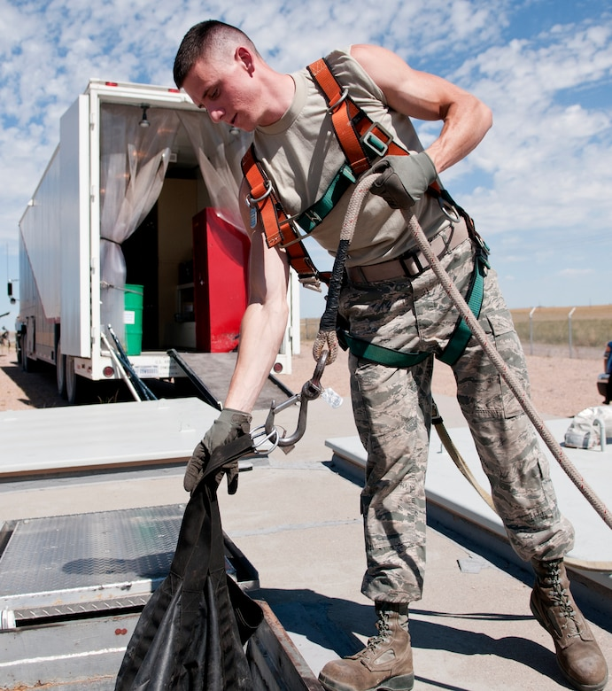 Airman 1st Class Coby Nette, 90th Missile Maintenance Squadron Periodic Maintenance Team technician, lowers equipment into the launch support building for a Minuteman III launch facility, in the F.E. Warren Air Force base, Wyo., missile complex, Sept. 2, 2015. Airmen are required to wear a safety harness to prevent injury to themselves whenever lowering items into LFs. (U.S. Air Force photo by Airman 1st Class Malcolm Mayfield)
