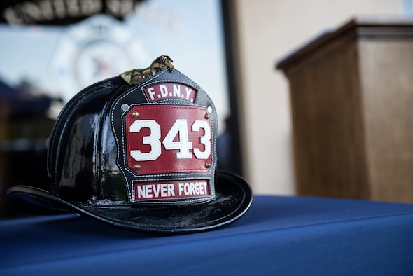 "A New York fire department helmet rests on a table with the words ""never forget"" written on it, symbolizes the heroic efforts made by those firefighters who rushed into the World Trade Center buildings during a 9/11 remembrance ceremony at Moody Air Force Base, Ga., Sept. 11 2015. (U.S. Air Force photo by Airman 1st Class Gregory Nash)"