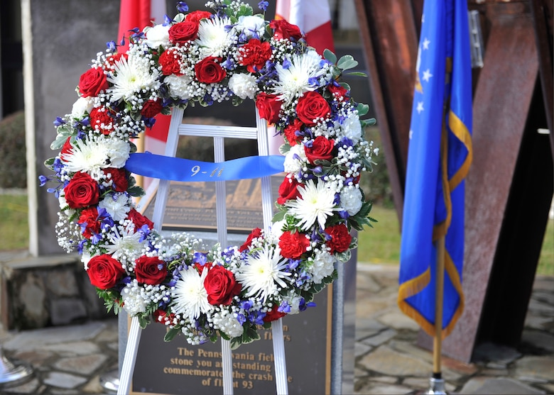 The wreath of red white and blue flowers stands in front of the charred granite stone from the Pentagon at the 601st Air Operations Center's 9/11 Memorial. Placement of the wreath was part of a remembrance ceremony there Sept. 11. (Air Force Photo Released/Airman 1st Class Sergio Gamboa)
