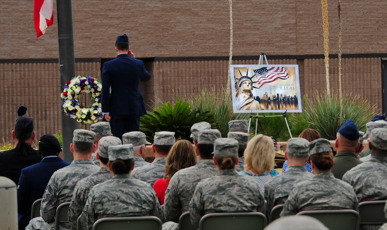 U.S. Air Force Col. Clint Eichelberger, 355th Operations Group commander, salutes a wreath to honor the victims of the September 11, 2001, terrorist attacks during a 9/11 remembrance ceremony at Davis-Monthan Air Force Base, Ariz., Sept. 11, 2015. Eichelberger spoke during the ceremony about how the passengers aboard United Airlines Flight 93 became the first individuals to fight against a new era of terrorism. (U.S. Air Force photo by Airman 1st Class Chris Drzazgowski/Released)