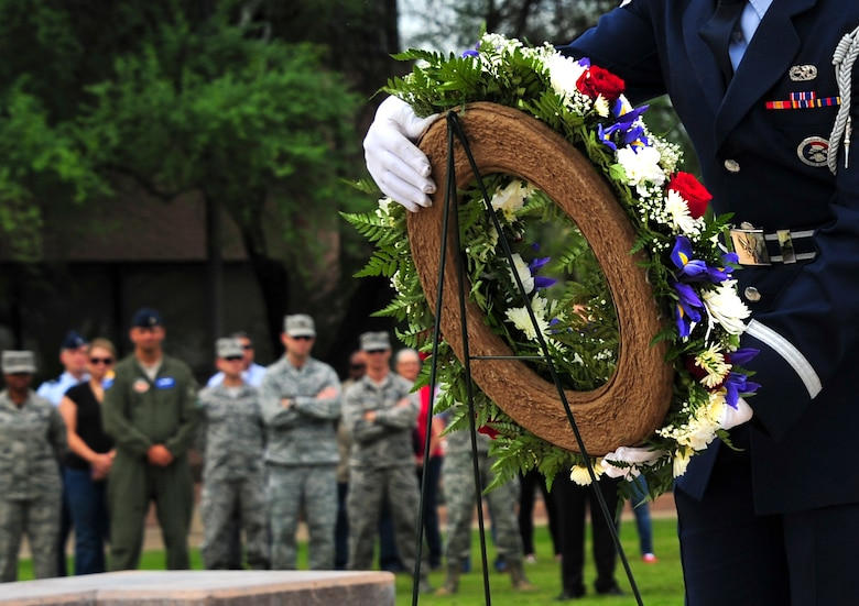 U.S. Air Force Senior Airman Braulio Torres, 355th Aircraft Maintenance Squadron crew chief, lays a wreath during a 9/11 remembrance ceremony at Davis-Monthan Air Force Base, Ariz., Sept. 11, 2015. More than 100 Airmen and civilians attended the ceremony to honor those who lost their lives in the Sept. 11, 2001, terrorist attacks. (U.S. Air Force photo by Airman 1st Class Chris Drzazgowski/Released)