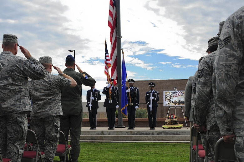 U.S. Airmen salute as the Davis-Monthan Air Force Base Honor Guard posts the colors during a 9/11 remembrance ceremony at Davis-Monthan AFB, Ariz., Sept. 11, 2015. The ceremony was in honor of the nearly 3,000 lives lost during the Sept. 11, 2001 terrorist attacks. (U.S. Air Force photo by Airman 1st Class Chris Drzazgowski/Released)