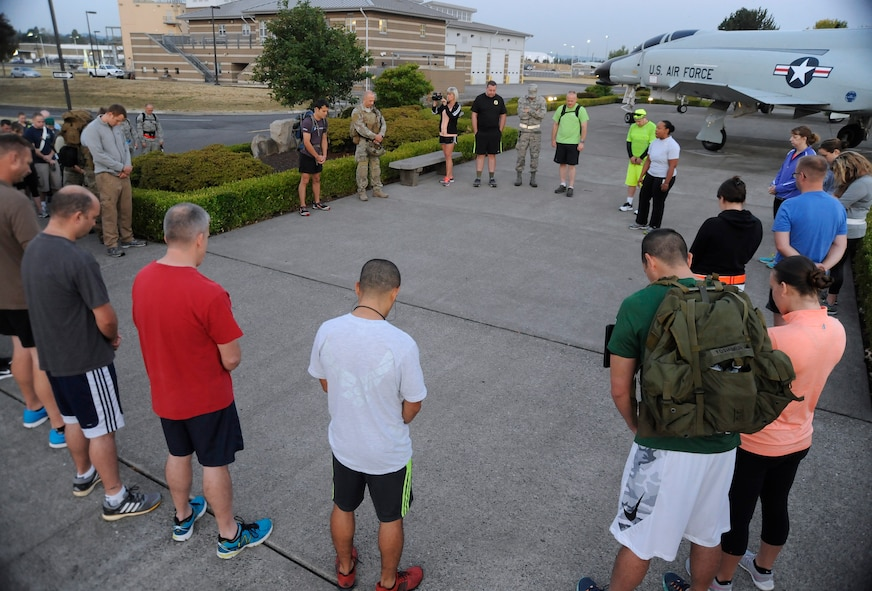 Participants for the 'Ruck, Run and Walk' gather for a morning message and prayer by Maj. Trisa Kelly, 142nd Fighter Wing Chaplain, Sept. 11, 2015, Portland Air National Guard Base, Ore. (U.S. Air National Guard photo by Tech. Sgt. John Hughel, 142nd Fighter Wing Public Affair/Released)