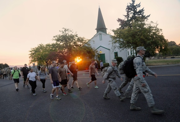 Participants from the 142nd Fighter Wing and 304th Rescue Squadron move along the route of the 'Ruck, Run and Walk', and pass the air base chapel at Portland Air National Guard Base, Ore., Sept 11, 2015. (U.S. Air National Guard photo by Tech. Sgt. John Hughel, 142nd Fighter Wing Public Affair/Released)