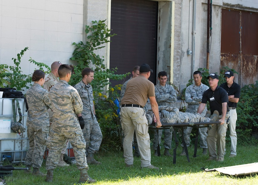 Participants in the Air Force Research Laboratory 2015 Tech Warrior exercise learn some of the basics of safely transporting a wounded service member on a stretcher, Sept. 10, 2015, at the National Center for Medical Readiness, Fairborn, Ohio. During the exercise participants are learning a variety of skills such as base defense, self-aide buddy care, tactical vehicle driving and land navigation. (U.S. Air Force photo by Wesley Farnsworth / Released)