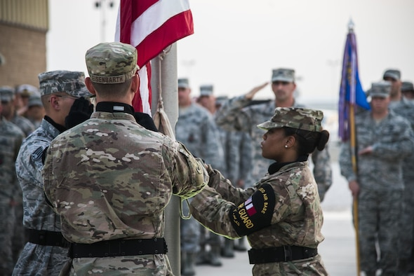 U.S. Air Force Airmen lower an American flag during a retreat ceremony recognizing the fourteenth anniversary of Sept. 11, 2001, at Al Udeid Air Base, Qatar, Sept. 11, 2015. The retreat ceremony signals the end of the official duty day and serves as a ceremony for paying respect to the flag. In this ceremony, respect was paid to the flag and the memory of those lost on Sept. 11, 2001. (U.S. Air Force photo/Tech. Sgt. Rasheen Douglas)