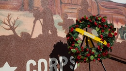 A wreath is laid beside the silhouette of a combat videographer following the unveiling of the Marine Week Phoenix mural in Scottsdale, Ariz., Sept. 12, 2015. The silhouette memorializes Lance Cpl. Jacob Hug, a Scottsdale native, who perished in a helicopter crash while the Corps was providing humanitarian assistance and disaster relief to Nepal.