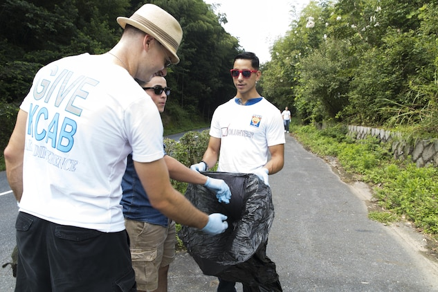 Sgt. Ryan Cipkar, left, and Lance Cpl. Miguel Avelar, center, dispose of trash as Lance Cpl. Miguel Moto holds the garbage bag open during a community relations event host by the Single Marine Program aboard Marine Corps Air Station Iwakuni, Japan, Sep. 4, 2015. Various organizations and tenant units aboard the air station foster the friendship between the U.S. and Japan by conducting these community relations events each year. Cipkar, from Steger, Ill., is a telephone person computer technician with Marine Tactical Electronic Warfare Squadron 3. Avelar, San Bernardino, Calif., and Moto, from Taipei, Taiwan, are expeditionary airfield system technician with Headquarters and Headquarters Squadron.