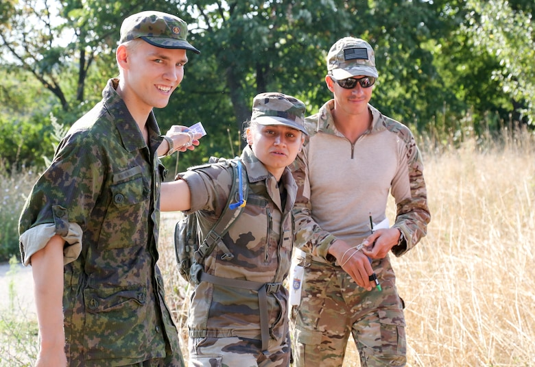 Maj. Peter Grossenbach (right), C-17 Globemaster III pilot with the 728th Airlift Squadron, pauses for a photo with his teammates 2nd Lt Student Tanali Karmeniemi (left), from Finland, and 2nd Lt Oceane Paul (middle), from France, during the orienteering competition at the Interallied Confederation of Reserve Officers, or CIOR, military competition in Shumen, Bulgaria, last month. After trying out and qualifying for Team USA Military, Grossenbach went on to represent the U.S. as part of an international team and won third place in the novice category. The pentathlon consists of: pistol shooting, rifle shooting, 500-meter land obstacle course, 50-meter water obstacle course, and up to a 15-kilometer orienteering, or land-navigation, event that also encompasses combat first aid. According to the CIOR Web site, the competition focuses on military skills that truly challenge the leadership and physical robustness of reservists. (Courtesy photo)