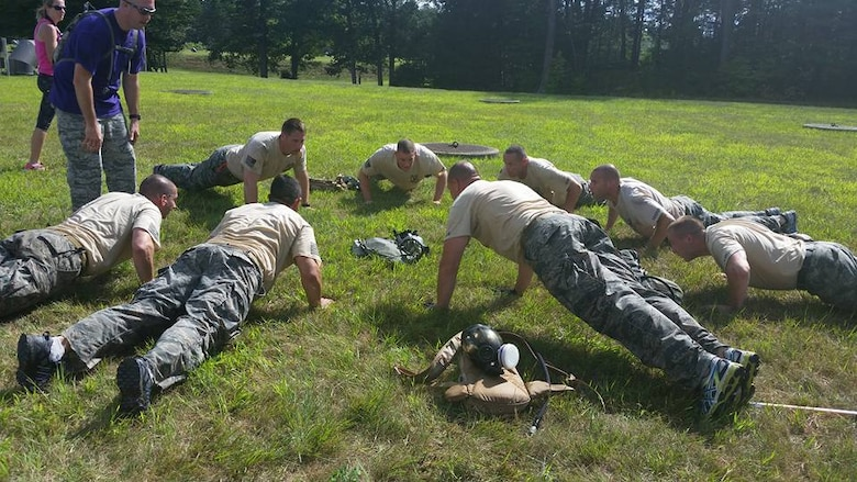 Select members of the 103rd Security Forces Squadron's CT SWAT Challenge team do group pushups as one of the many events of the challenge while team captain Staff Sgt. Michael Stearns looks on. The competitors banded up to compete in the challenge at two venues, the State Police Metacon Range in Simsbury and the MDC Reservoir in West Hartford, Conn., Sept. 17-21, 2015. (U.S. Air National Guard photos by Tech. Sgt. Jessica Roy)