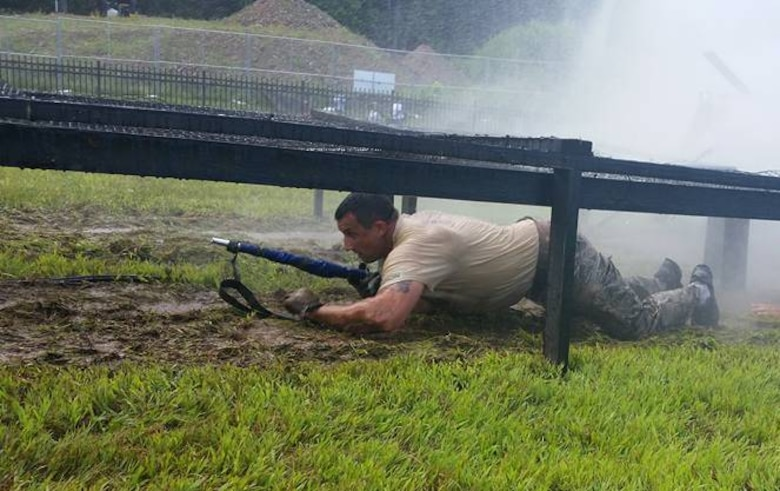 Tech. Sgt. Ian McMahon belly crawls with the unit's guidon through the water tunnel obstacle during the annual competition, CT SWAT Challenge. Select members of the 103rd Security Forces Squadron banded up to compete in the challenge at two venues, the State Police Metacon Range in Simsbury and the MDC Reservoir in West Hartford, Conn., Sept. 17-21, 2015. (U.S. Air National Guard photos by Tech. Sgt. Jessica Roy)