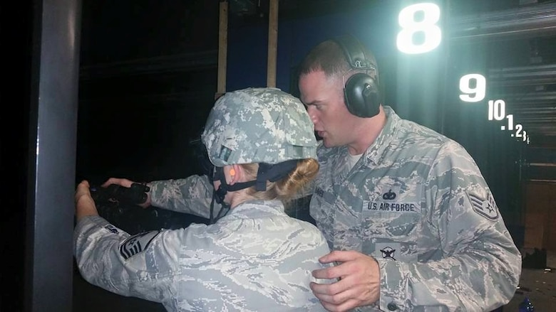 Staff Sgt. Brian Davies assists Master Sgt. Susan Flannery as she shoots using night vision goggles and a targeting laser at the Enfield Department of Corrections indoor firing range Aug. 1, 2015.  (U.S. Air National Guard photos by Tech. Sgt. Jessica Roy)