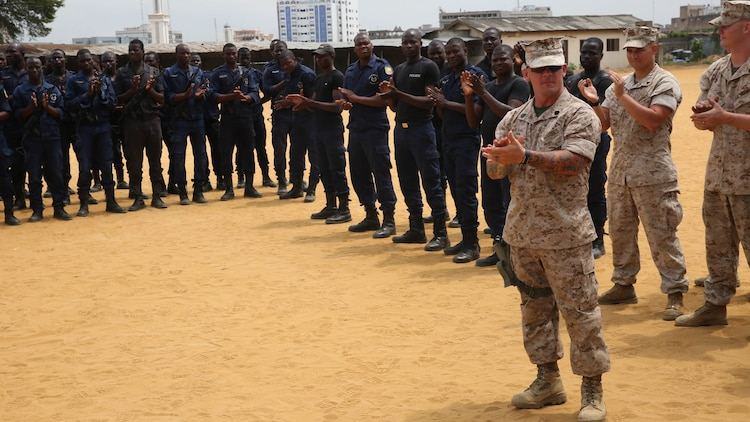 Benin National Surveillance Police commemorated the Sept. 11, 2001 anniversary attacks with U.S. Marines and sailors at the National Police Academy in Cotonou, Benin, today. The Marines and sailors with Special-Purpose Marine Air-Ground Task Force Crisis Response-Africa are in Benin for a month-long training mission with the National Surveillance Police to help counter  illicit trafficking along the country's borders. During a break in the training, NPS students stood alongside Marines and sailors in formation for a brief ceremony to remember the day when more than 3,000 lives perished from the heinous terrorist attack. The ceremony began with the playing of taps, followed by three smoke cans, releasing colors of the Benin flag, symbolizing the partnership between the U.S. and Benin.