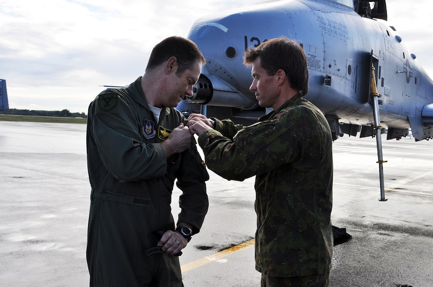 A-10 Thunderbolt II pilot, Lt. Col. Michael Leonas, 303d Fighter Squadron, exchanges uniform patches with Capt. Darius Kaleda of the Lithuanian Air Force at Kaunas Airport in Lithuania Sept. 9. Leonas flew in as part of Operation Atlantic Resolve where the U.S. is partnering and strengthening their relationship with European NATO allies. (U.S. Air Force photo by Capt. Denise Haeussler)