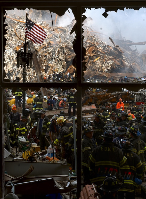 New York City firemen walk past the American flag as they work their way toward the heart of the devastation that was once the World Trade Center. (U.S. Navy Photo/Journalist 1st Class Preston Keres)