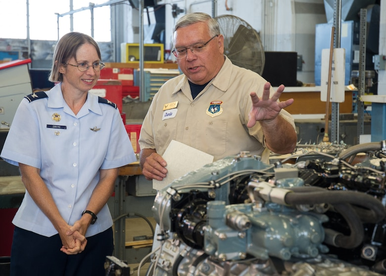 "DAYTON, Ohio -- 88th Air Base Wing Vice Commander Col. Elena M. Oberg (left) views a restored engine with Huber Heights resident Charles Farlow Jr. (right). Farlow was awarded the Team Wright-Patt ""Volunteer of the Quarter"" award for the second quarter of 2015 on Sept. 14, 2015. (U.S. Air Force photo)"