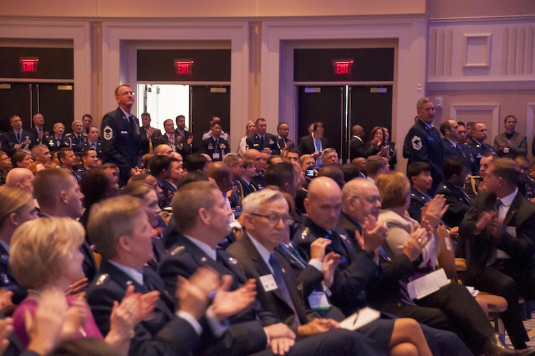 "Crew members from the 920th Rescue Wing who participated in the June 2005 rescue of Marcus Luttrell, a U.S. Navy SEAL, stand to be recognized during the Air Force Association Air and Space Conference and Technology Exposition, Washington D.C., Sept. 14, 2015. The well-known rescue was dramatized in the movie ""The Lone Survivor."" (U.S. Air Force photo/Staff Sgt. Kat Justen)"