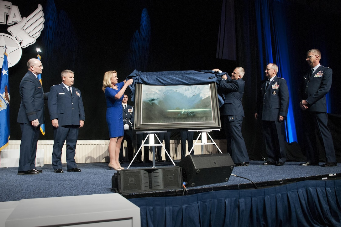 "Air Force Secretary Deborah Lee James and Maj. Warren Neary, the Air Force Space Command historian and an Air Force Art Program artist, unveil the painting ""That Others May Live"" during the Air Force Association Air and Space Conference and Technology Exposition, Washington, D.C., Sept. 14, 2015. ""That Others May Live"" documents the rescue of Marcus Luttrell, a Navy SEAL, in June 2005 by Reservists from the 920th Rescue Wing at Patrick Air Force Base, Florida. The rescue was dramatized in the movie ""The Lone Survivor."" (U.S. Air Force photo/Staff Sgt. Kat Justen)"