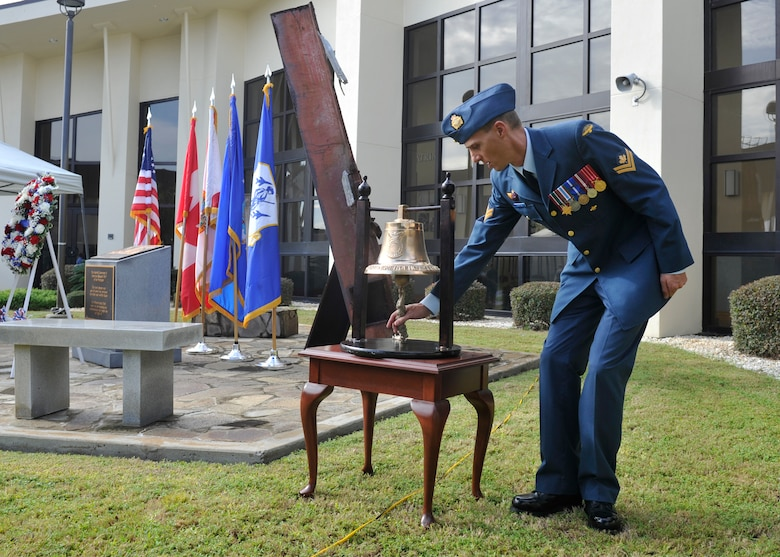 Royal Canadian Air Force MCpl Craig Robertson, 101st Air Communications Squadron, tolls the ceremonial bell from the 325th Fighter Wing Fire Department during the 9/11 remembrance ceremony at the 601st Air Operations Center. The ceremony was held to honor and remember all who were affected by the tragic events of that day. (Air Force photo released/Airman 1st Class Sergio Gamboa)