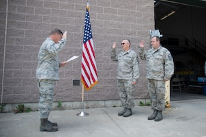 Capt. Frank King administers the oath of re-enlistment to uncle and cousin, Chief Master Sgt. Craig Sanborn and Master Sgt. Chirs Sanborn at the 158th Fighter Wing in South Burlington, Vt., Aug. 6, 2015. It is a rare occasion at the Vermont Air National Guard that three family members are involved in such an honorable event. (U.S. Air National Guard photo by Airman 1st Class Jeffrey Tatro)