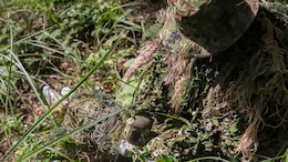 Japan Ground Self-Defense Force Sgt. Akito Yagi attaches vegetation to his sniper rifle while performing stalking drills during Forest Light 16-1 at Camp Imazu, Takashima, Japan, Sept. 10, 2015. The Marines sat up on a high embankment, trying to catch the JGSDF stalking the target with binoculars. Forest Light is a semiannual, bilateral exercise consisting of a command post exercise and multiple field training events, conducted by elements of III Marine Expeditionary Force and the JGSDF. Yagi is a sniper with 50th Infantry Regiment, 14th Brigade.