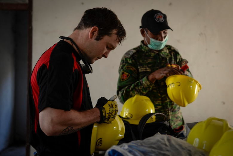 Sapper Reece Stairmand, a Pacific Angel 15-2 carpenter from New Zealand, and a member of the Falintil Forças de Defesa de Timor-Leste, write their names on protective helmets before beginning work on a Pacific Angel 15-2 construction project Sept. 5, 2015, in Baucau, Timor-Leste. Efforts undertaken during Pacific Angel help multilateral militaries in the Pacific improve and build relationships across a wide spectrum of civic operations, which bolsters each nation's capacity to respond and support future humanitarian assistance and disaster relief operations. (U.S. Air Force photo by Staff Sgt. Alexander W. Riedel/Released)