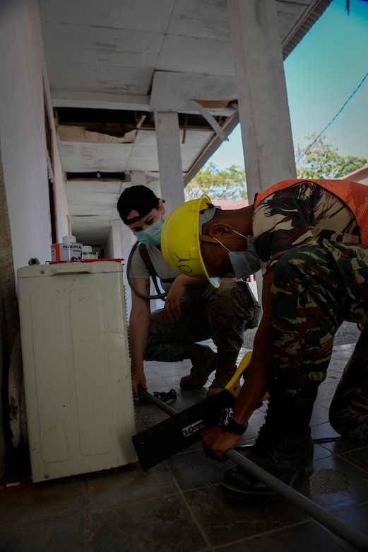 Senior Airman Blake Brooks, Pacific Angel 15-2 plumber, shortens a pipe with the help of Private Vitorino de Jesus Pereira, a soldier with Falintil Forças de Defesa de Timor-Leste, during a PACANGEL engineering project Sept. 5, 2015, in Baucau, Timor-Leste. Efforts undertaken during Pacific Angel help multilateral militaries in the Pacific improve and build relationships across a wide spectrum of civic operations, which bolsters each nation's capacity to respond and support future humanitarian assistance and disaster relief operations. (U.S. Air Force photo by Staff Sgt. Alexander W. Riedel/Released)