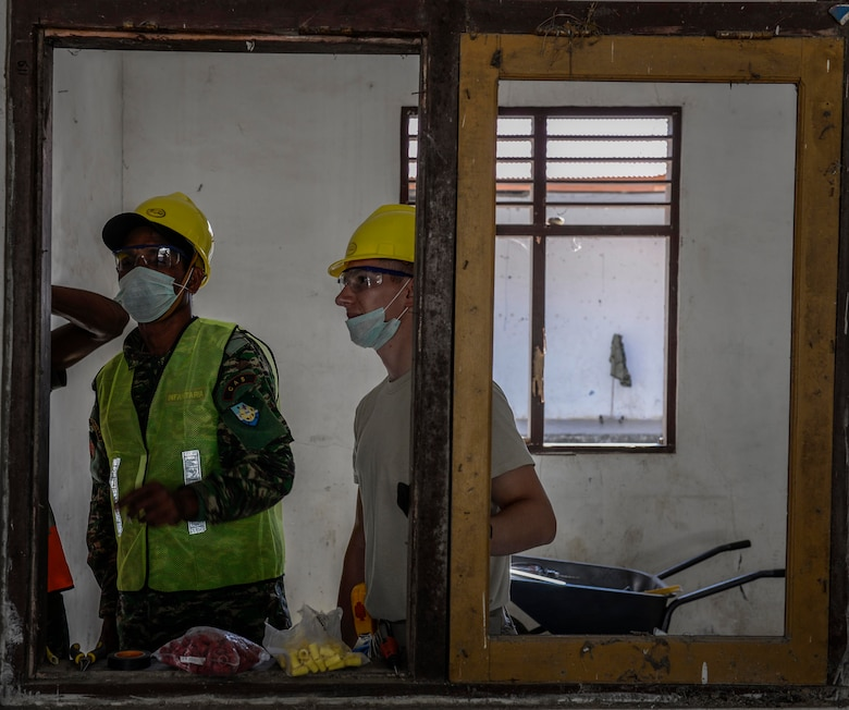 Senior Airman Zachary Hambright, Pacific Angel 15-2 electrician, studies an electrical connection with soldiers of the Falintil Forças de Defesa de Timor-Leste, during a PACANGEL engineering project Sept. 5, 2015, in Baucau, Timor-Leste. Efforts undertaken during Pacific Angel help multilateral militaries in the Pacific improve and build relationships across a wide spectrum of civic operations, which bolsters each nation's capacity to respond and support future humanitarian assistance and disaster relief operations. (U.S. Air Force photo by Staff Sgt. Alexander W. Riedel/Released)