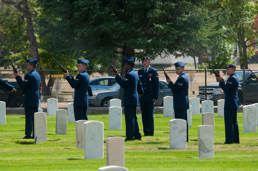A team of new ceremonial guardsmen from the 90th Missile Wing prepare to fire a volley during a display of their role in a military funeral Sept. 11, 2015, in the F.E. Warren Air Force Base, Wyo., cemetery. The demonstration was part of the Airmen's graduation, marking the end of their training to join the honor guard. (U.S. Air Force photo by Senior Airman Jason Wiese)