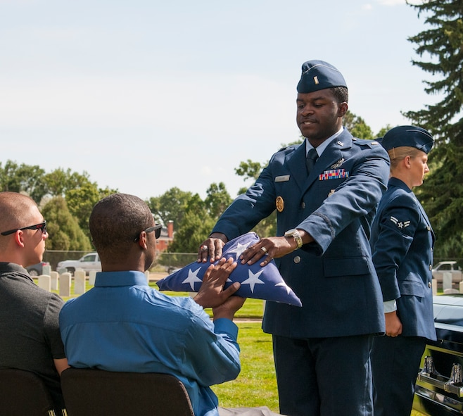 Second Lt. Darrell Cousin, 319th Missile Squadron ICBM deputy combat crew commander and newly graduated 90th Missile Wing ceremonial guardsman, presents a folded American Flag to an Airman portraying the loved one of a deceased Airman Sept. 11, 2015, in F.E. Warren Air Force Base, Wyo., cemetery during a display of what ceremonial guardsmen do during military funerals. The demonstration was part of the Airmen's graduation, marking the end of their training to join the honor guard. (U.S. Air Force photo by Senior Airman Jason Wiese)